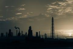 Het silhouet van de olieraffinaderij bij zonsopgang Stock Foto