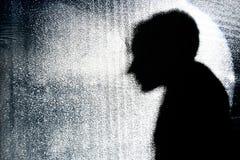 Het silhouet van de persoon achter glasmuur Stock Foto's
