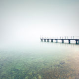 De pijler of de pier silhouetteert in een mistig meer. Het meer van Garda, Italië Stock Foto