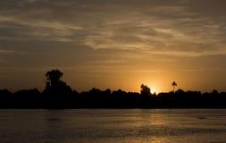 Het silhouet van de rivierbank bij schemerzonsondergang Stock Afbeelding