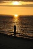 Het silhouet van de visser bij zonsondergang. Stock Fotografie