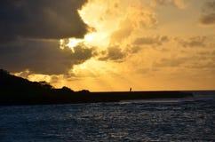 Het silhouet van de visser bij zonsondergang Royalty-vrije Stock Foto
