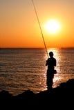 Het silhouet van de visser bij zonsondergang Stock Afbeeldingen