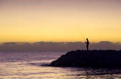 Het silhouet van de visser bij zonsopgang Stock Fotografie