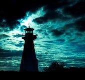 Het silhouet van de vuurtoren tegen onheilspellende hemel. stock fotografie