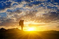 Het silhouet van de wandelaar bij de zonsondergang Stock Afbeelding
