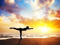Het silhouet van de yoga op het strand
