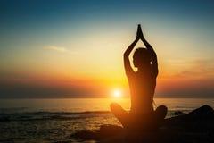 Het silhouet van de yogavrouw Meditatie op de oceaan ontspan stock fotografie