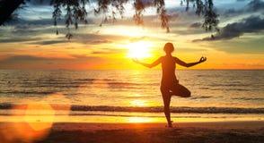 Het silhouet van de yogavrouw Oefeningen op het strand tijdens een mooie zonsondergang royalty-vrije stock foto's