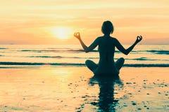 Het silhouet van de yogavrouw op het overzeese strand stock afbeeldingen