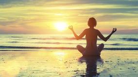 Het silhouet van de yogavrouw op het overzeese strand bij zonsondergang ontspan stock afbeeldingen