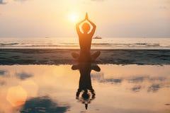 Het silhouet van de yogavrouw op het strand, heldere zonsondergang ontspan stock afbeelding