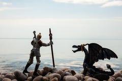 Het silhouet van draak en ridder op pebbled kust Stock Afbeelding