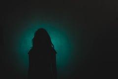 Het silhouet van drukt vrouw status in dark met licht scheenbeen in stock foto's