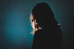 Het silhouet van drukt vrouw status in dark met licht scheenbeen in Royalty-vrije Stock Foto