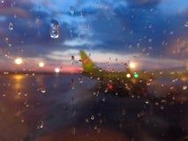 Het silhouet van een bevindend vliegtuig bij de luchthaven door het glas met regendruppels royalty-vrije stock foto's