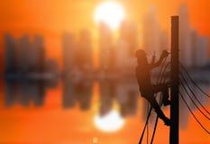 Het silhouet van een elektricien beklimt op elektrische pool royalty-vrije stock foto