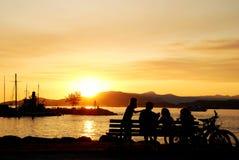 Het silhouet van een familie geniet van mooie zonsondergangmening Stock Foto's