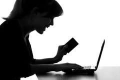 Het silhouet van een jonge vrouw krijgt bonusefrom een online aankoop stock afbeeldingen