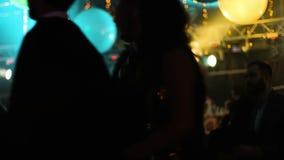 Het silhouet van een langharige vrouw danst in een nachtclub bij een partij, volledig van geluk en enthousiast meisje is stock video