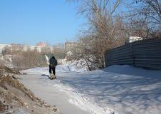 Het silhouet van een lopende mens draagt een ar in de winter stock afbeelding