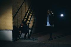 Het silhouet van een man valt erachter een vrouw van in een donkere tunnel aan Geweld tegen Vrouwenconcept De ruimte van het exem Stock Afbeelding