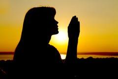 Het silhouet van een meisje heft handen aan God op royalty-vrije stock afbeeldingen