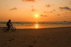 Het silhouet van een mens berijdt een fiets bij zonsondergang De mensenoefening langs Stock Foto's