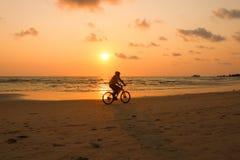 Het silhouet van een mens berijdt een fiets bij zonsondergang De mensenoefening langs Royalty-vrije Stock Afbeelding