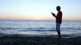 Het silhouet van een mens bij zonsondergang gaat langs de waterkant met een tabletcomputer over Hij houdt, controleert het berich stock video