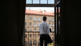 Het silhouet van een mens draagt een jasje die zich op het balkon van het hotel bevinden stock videobeelden