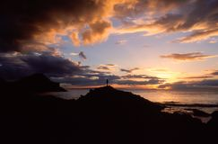 Het silhouet van een mens in het natuurlijke landschap van een zonsondergang over stock afbeeldingen