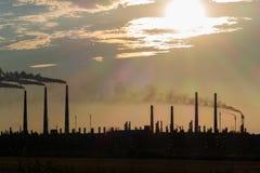 Het silhouet van een reusachtige gas en olieverwerkingsinstallatie met het branden van toortsen, pijpen en distillatie van het co royalty-vrije stock afbeeldingen