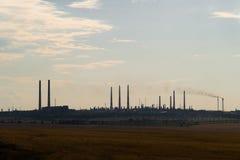 Het silhouet van een reusachtige gas en olieverwerkingsinstallatie met het branden van toortsen, pijpen en distillatie van het co Royalty-vrije Stock Foto