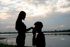 Het silhouet van een romantisch paar die, elkaar koesteren en op de zonsondergang letten bevinden zich Romaans en liefdeconcept stock afbeeldingen