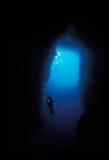 Het silhouet van een scuba-duiker die in een hol zwemmen royalty-vrije stock afbeeldingen