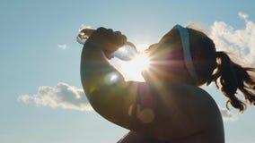 Het silhouet van een vet meisje drinkt water van een fles stock video