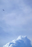 Het silhouet van een vliegend vliegtuig op heldere blauwe bewolkte hemel met cumulus betrekt hieronder bij Royalty-vrije Stock Foto