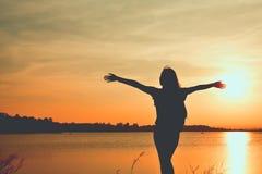 Het silhouet van gelukkige vrouwen ontspant in de aard Stock Foto