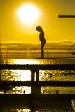 Het silhouet van het aarzelingsmeisje op de 3m springplank Royalty-vrije Stock Afbeeldingen