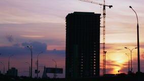 Het silhouet van het bouwproject tegen zonsonderganghemel Stadslandschap met auto's en bouwwerf stock footage