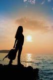 Het silhouet van het meisje met rugzak bij zonsondergang royalty-vrije stock foto's