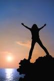 Het silhouet van het meisje met rugzak bij zonsondergang stock foto's