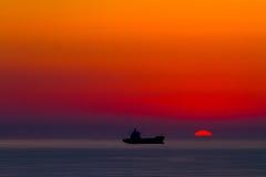 Het silhouet van het schip bij zonsondergang Stock Foto