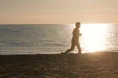 Het silhouet van Jogger op strand stock afbeelding