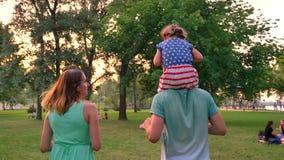 Het silhouet van jonge familie loopt in park in de zomer, zit het meisje op vader` s schouders, zonsondergang stock videobeelden