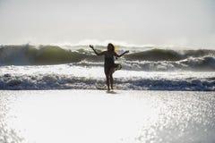 Het silhouet van jonge gelukkige Aziatische vrouw ontspande het bekijken wilde overzeese golven op zonsondergang tropisch strand Royalty-vrije Stock Foto's
