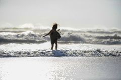 Het silhouet van jonge gelukkige Aziatische vrouw ontspande het bekijken wilde overzeese golven op zonsondergang tropisch strand Royalty-vrije Stock Foto