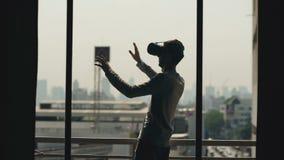 Het silhouet van jonge mens het letten op film in VR-hoofdtelefoon en heeft virtuele werkelijkheidservaring op het balkon van de
