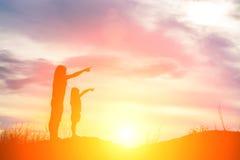 Het silhouet van jonge moeder richtte de vinger aan de toekomst stock afbeelding
